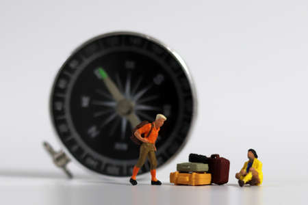 A miniature man standing in front of the compass and a miniature woman sitting with luggage. Compass and miniature people.