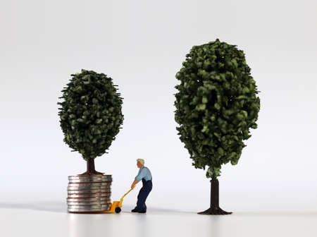 Piles of coins and miniature trees and miniature man.