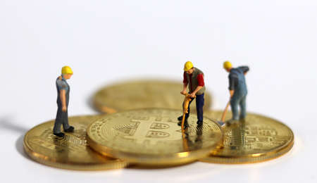 Miniature people holding tools on Bitcoin. Miniature people and business concept. 版權商用圖片