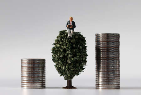 Piles of coins and miniature tree and miniature man
