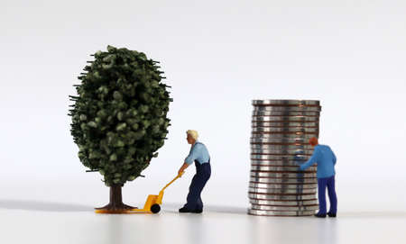 Piles of coins and miniature tree and miniature people.