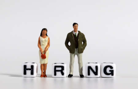 The concept of hiring employees. A miniature man and woman standing with a cube with a HIRING word.