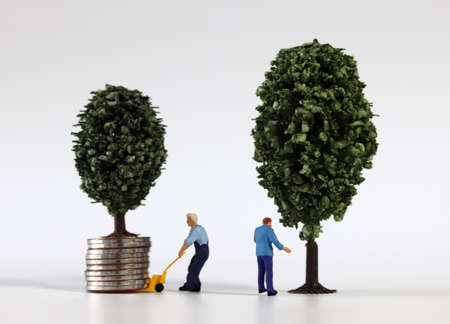 Piles of coins and miniature trees and miniature people. Miniature people and business concept.