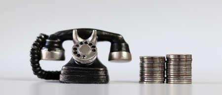 Miniature phone and coins on background.