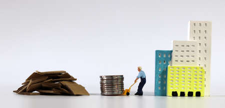 A miniature man carrying a pile of coins in a cart next to a pile of junk. Miniature people and business concept.