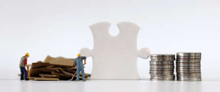 Miniature people and business concept. A piece of puzzle between a pile of paper and a pile of coins. 版權商用圖片