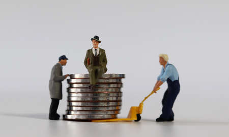 Miniature people and piles of coins. Two miniature people carrying a miniature man sitting on a pile of coins into a cart. 版權商用圖片