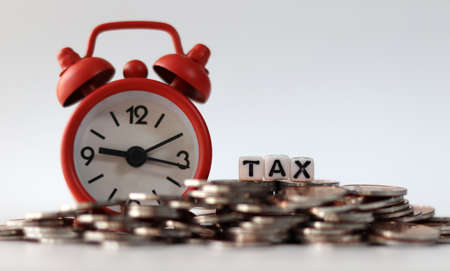 coins, clock and tax on background.