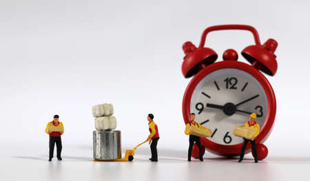 Miniature deliverymen holding parcels. A miniature man carrying a red alarm clock.