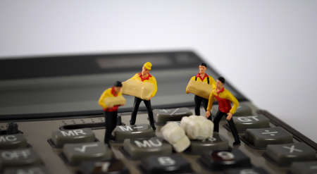 Four miniature couriers standing on a calculator. 版權商用圖片