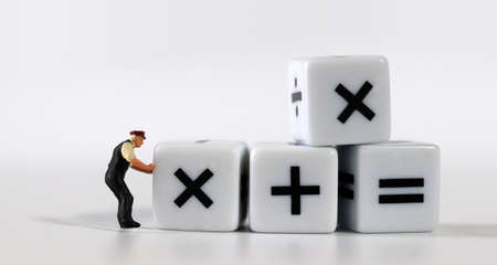 white dice with mathematical math symbols and miniature man