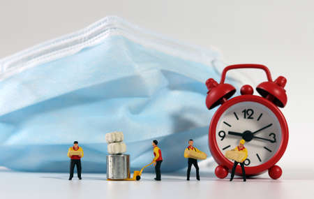 Miniature deliverymen holding parcels, red alarm clock. 版權商用圖片