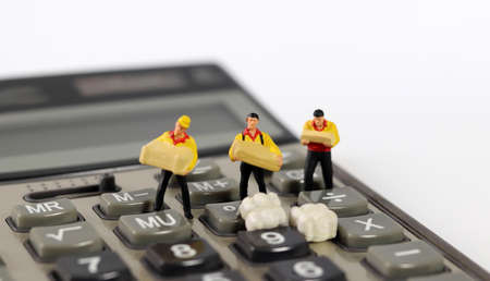 Three miniature couriers standing on a calculator. 版權商用圖片