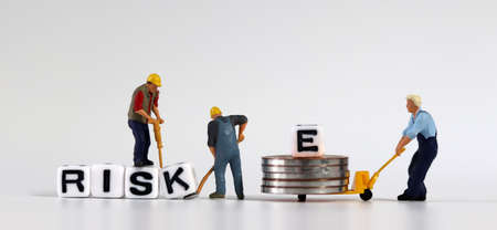 Miniature people who change cubes with RISK into RISE. Miniature man carrying E and coins in a cart.
