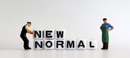Cube with New Normal and two miniature men. The concept of preparing a New Normal.