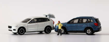 Two miniature cars collided with Miniature man calling. Concepts about car accidents and miniature people. 版權商用圖片