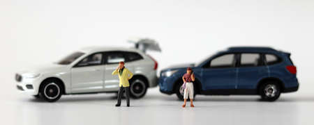 Two miniature cars collided and two miniature people calling. Concepts about car accidents and miniature people.