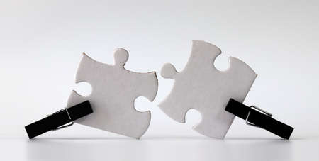 Black wooden tongs and two white puzzles. Puzzle pieces and business concepts.