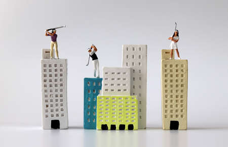 Miniature people playing golf on miniature buildings. The concept of inequality in wealth. 版權商用圖片