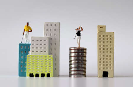 A miniature man playing golf in a miniature building and a pile of coins. The concept of successful real estate investment.
