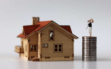 A miniature man playing golf in a miniature house and a pile of coins. The concept of successful real estate investment.