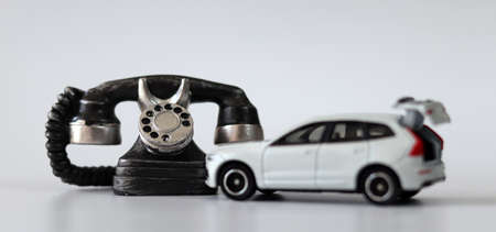 Miniature phones and broken white miniature cars. The concept of traffic accident reception. 版權商用圖片