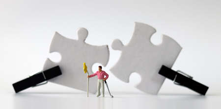 Miniature man standing in front of Black wooden tongs and two white puzzles. Puzzle pieces and business concepts.