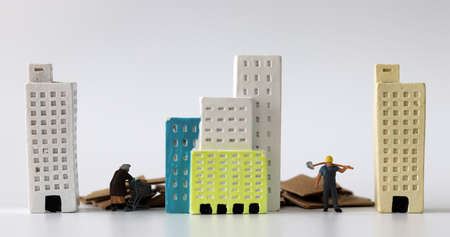 Miniature people between miniature buildings. The concept of the deepening gap between the rich and the poor. Stock fotó