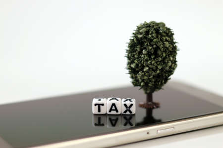 A white cube with the word'TAX' and a miniature tree on the Smartphone. Concept of online tax payment. 版權商用圖片