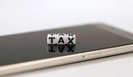A white cube with the word'TAX' on the Smartphone. Concept of online tax payment.