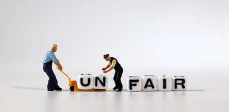 Two miniature men moving the cube of'UN' word from cube with'FAIR' word to cart. White cube with words and miniature people.