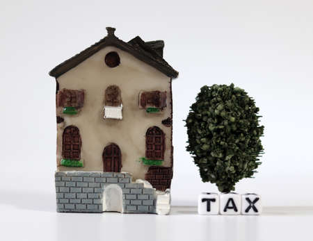 A white cube with the word'TAX' with a miniature house. The concept of increasing real estate taxes.
