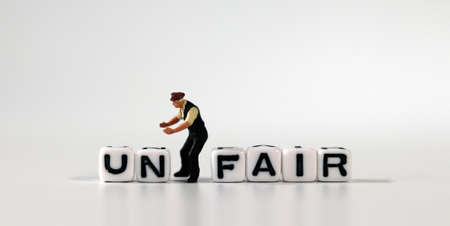 The word UN on white cubes and the word FAIR on white cubes. White cube with words and miniature people. Stock fotó