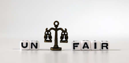 Miniature scale between cube with word'UN' and cube with word'FAIR'. The concept of a fair society. Stock fotó
