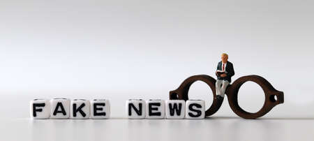 White dice and'FAKE NEWS' with News, solution and business concepts on white background. White cube and miniature people.