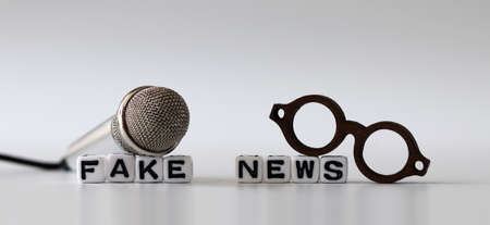 White dice and'FAKE NEWS' with News, solution and business concepts on white background. White cube, miniature microphones and miniature glasses.