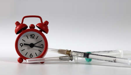 Syringe and a red alarm clock. Concept of the importance of vaccination.