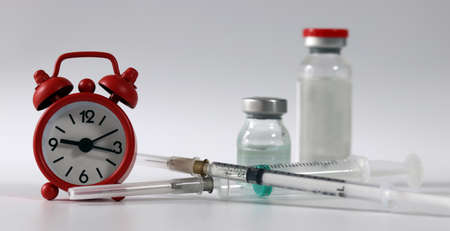 Syringe and vaccine vial with a red alarm clock. Concept of the importance of vaccination. Stock Photo