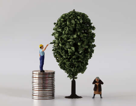 A miniature man and a miniature woman on a pile of coins next to a miniature tree. The concept of economic inequality.