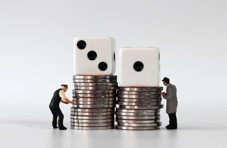 Pile of coins and two white dice. Miniature people and business concept. Stock Photo