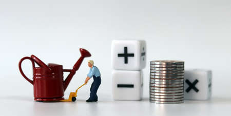 A miniature man carrying a red watering can with a handcart and a white cube with arithmetic symbols. Miniature people and coin and business concept. Stock Photo