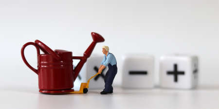 A miniature man carrying a red watering can with a handcart and a white cube with arithmetic symbols. Miniature people and business concept.