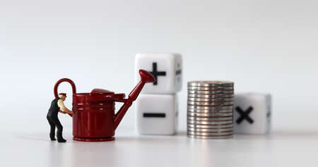 A watering can and a miniature man. A white cube with coins and arithmetic symbols. Stock Photo
