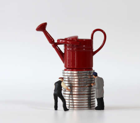 Red miniature watering can on a pile of coins and two miniature people. Miniature people and coin and business concept.