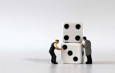 Two dice and two miniature men. Miniature people and business concept.