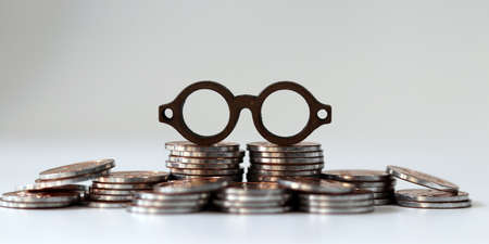 Miniature eyeglasses on a pile of coins. The concept of the importance of information analysis prior to successful investment.