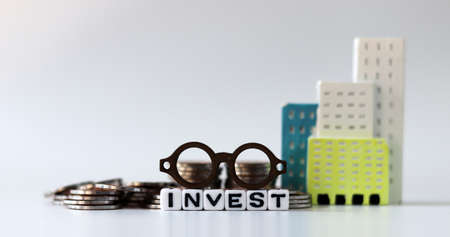 A miniature eyeglasses on White cube bearing the word 'INVEST' with a bundle. The concept of real estate investment. Stock fotó