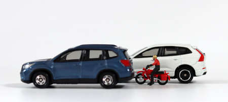 A motorcycle driver between a blue car and a white car. Miniature people and miniature cars.