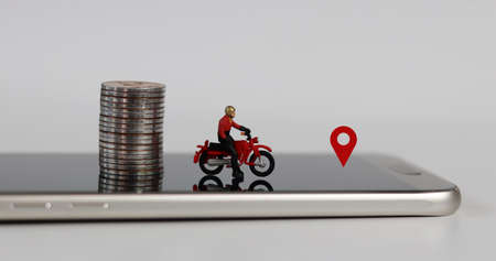 Smartphones and miniature people. A miniature motorcycle rider with a red location mark and coins on the smartphone.