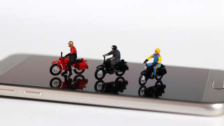 Three miniature motorcycle riders on the smartphone. Concept about useful online delivery. 版權商用圖片